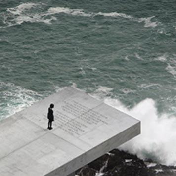 Joven de pie una pasarela de hormigón al borde del mar