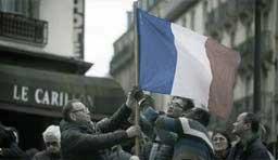 Tres personas colocan una bandera francesa en una calle de París