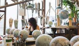 Una mujer trabaja en un taller lleno de globos terráqueos